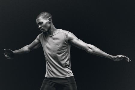 lanzamiento de disco: Vista frontal del deportista practicando el lanzamiento de disco contra el fondo negro