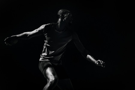 discus: Athlete man throwing a discus against black background