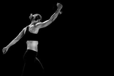 lanzamiento de disco: Vista lateral de la mujer deportiva que prepara su lanzamiento de disco contra el fondo negro