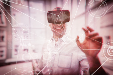 connectivity: Various graphs and connectivity points  against smiling graphic designer using virtual reality headset Stock Photo