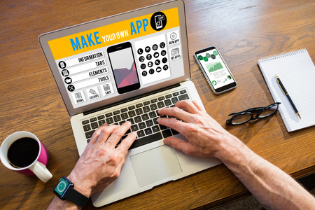 using smartphone: Make your own app smartphone against businessman using a laptop Stock Photo