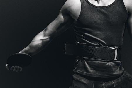 lanzamiento de disco: Ciérrese para arriba en el pecho deportista practicando el lanzamiento de disco contra el fondo negro