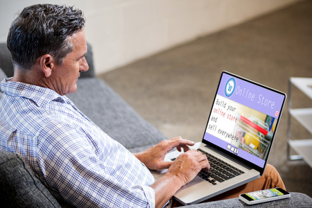 mature business man: Screen of an online store against profile view of a businessman working on computer Stock Photo