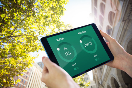 tress: Hands holding tablet against low angle view of buildings and tress