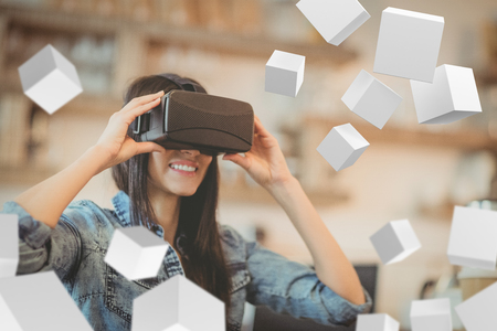 Digitally generated grey cubes floating  against young woman using the virtual reality headset
