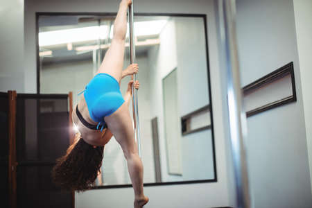 poledance: Pole dancer practicing pole dance in fitness studio
