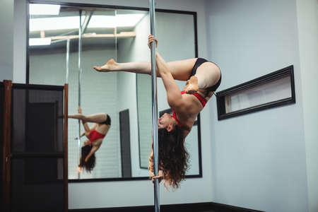 pole dance: Pole dancer practicing pole dance in fitness studio