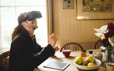 virtual reality simulator: Happy hipster enjoying while using virtual reality simulator at home