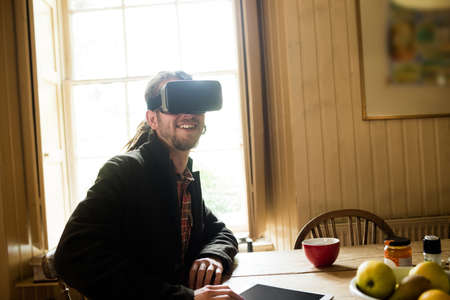 virtual reality simulator: Smiling young man using virtual reality simulator at home