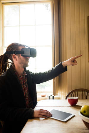 virtual reality simulator: Hipster pointing while wearing virtual reality simulator at home
