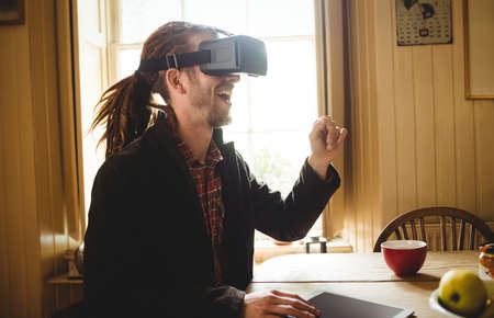 virtual reality simulator: Happy young man using virtual reality simulator at home LANG_EVOIMAGES