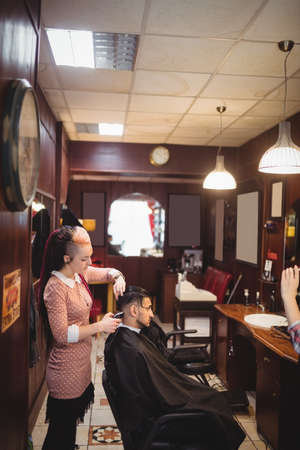 trimmed: Man getting his hair trimmed with trimmer in barber shop