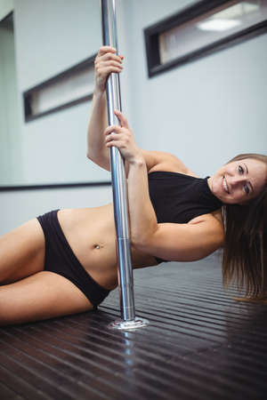 pole dancer: Portrait of pole dancer holding pole in fitness studio