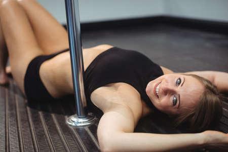pole dancer: Portrait of pole dancer lying on the floor in fitness studio