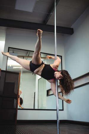pole dance: Pole dancer practicing pole dance in fitness studio