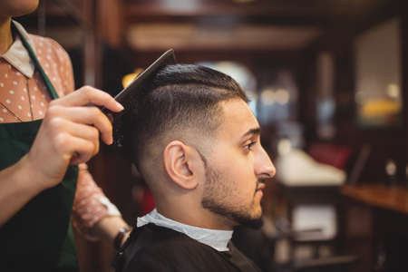 indian style sitting: Man getting his hair trimmed in barber shop