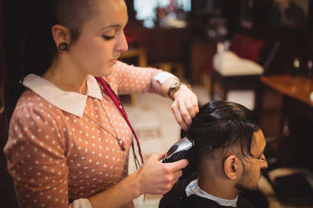 trimmer: Man getting his hair trimmed with trimmer in barber shop