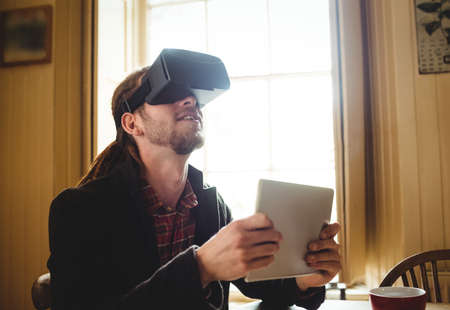virtual reality simulator: Hipster holding digital tablet while using virtual reality simulator at home