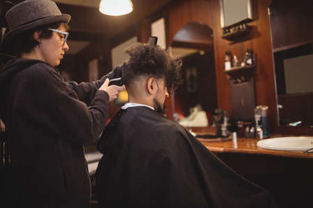 indian style sitting: Man getting his hair trimmed with trimmer in barber shop