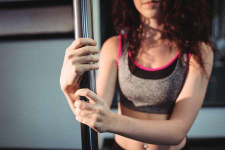 pole dancer: Close-up of pole dancer holding pole in fitness studio