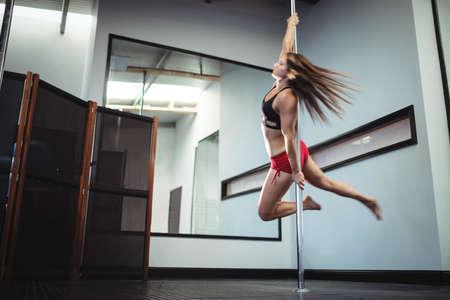 pole dancer: Pole dancer practicing pole dance in fitness studio