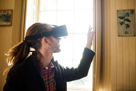 virtual reality simulator: Close-up of hipster gesturing while using virtual reality simulator at home