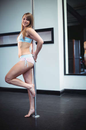 pole dancer: Portrait of pole dancer leaning against pole in fitness studio