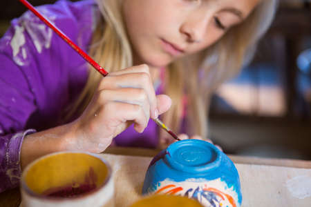 attentive: Attentive girl painting on bowl in pottery workshop