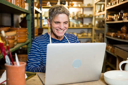 potter: Happy male potter using laptop in pottery workshop