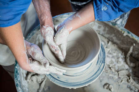 alfarero: Mid section male potter assisting female potter in pottery workshop