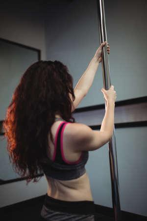 pole dancer: Pole dancer holding pole in fitness studio