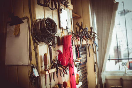 repairer: Old horologists workshop with clock repairing tools and equipments on wall