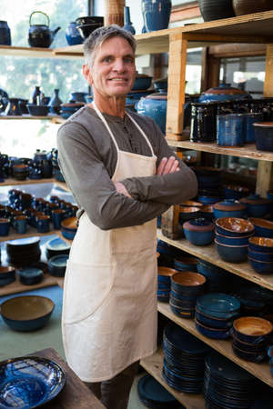 potter: Happy male potter standing with arms crossed in pottery workshop
