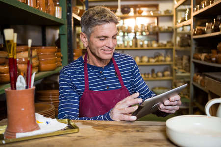 gente adulta: alfarero de sexo masculino que usa la tableta digital en taller de cerámica