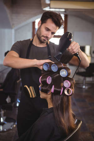 hair roller: Male hairdresser styling customers hair at a salon