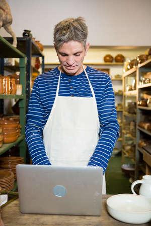 alfarero: alfarero de sexo masculino con ordenador portátil en taller de cerámica LANG_EVOIMAGES