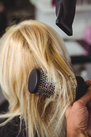 secador de pelo: Mujer que consigue el pelo se seca con secador de pelo en peluquería