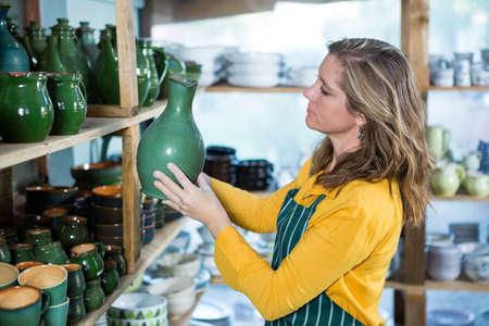 alfarero: alfarero Mujer colocando olla en estante en taller de cer�mica
