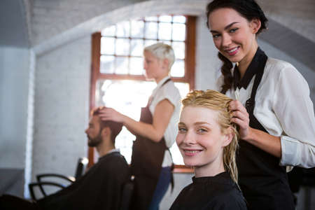 stylist: Portrait of smiling hair stylist massaging clients hair in salon
