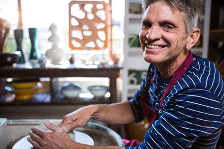 alfarero: Portrait of happy male potter making pot in pottery workshop