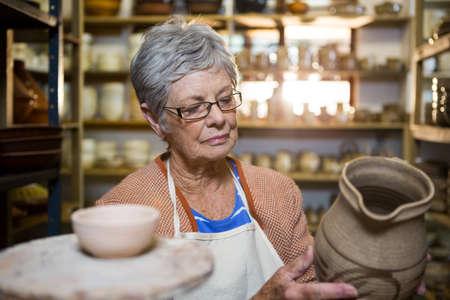 alfarero: Mujer pote alfarero comprobación en taller de cerámica