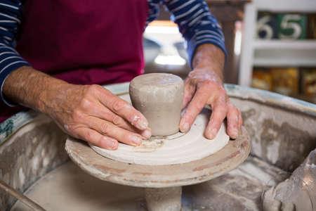 alfarero: Mid section of potter making pot in pottery workshop LANG_EVOIMAGES