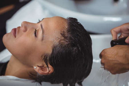 rinsing: Woman getting her hair wash at a salon LANG_EVOIMAGES