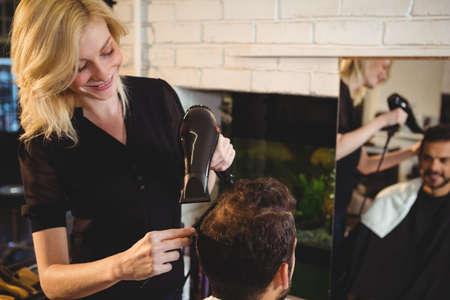 secador de pelo: El hombre sonriente que consigue el pelo se seca con secador de pelo en el sal�n LANG_EVOIMAGES