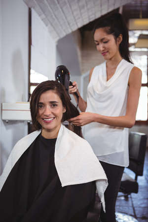 secador de pelo: Portrait of woman getting her hair dried with hair dryer at the hair salon