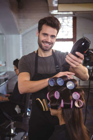 hair roller: Portrait of smiling male hairdresser styling customers hair at a salon