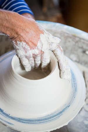 potter: Close-up of potter making pot in pottery workshop