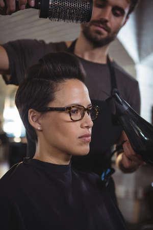 secador de pelo: mujer obtener su cabello se seca con el secador de pelo en la peluquería