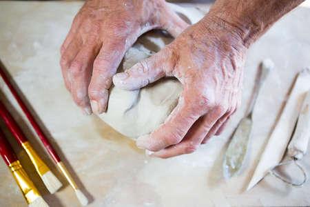 potter: Close-up potter molding clay in pottery workshop LANG_EVOIMAGES