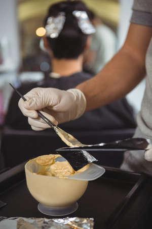 tinte de cabello: Mediados de la sección de peluquería femenina preparar un plato de tinte para el cabello en el salón